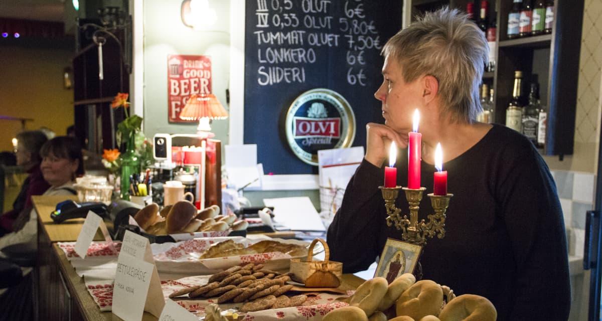 Anita Raatevaara kuuntelee runolaulua. Hänen edessään on pöytä täynnä vienankarjalaisia ruokia.