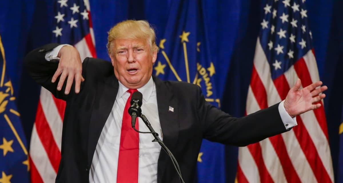 Donald Trump viittilöi puhuessaan mikrofoniin. Hänellä on tumma puku, valkoinen kauluspaita ja punainen kravatti. Takin rintapielessä on Yhdysvaltain lippua esittävä pinssi. Taustalla näkyy Yhdysvaltain lippuja ja Indianan osavaltion lippuja.
