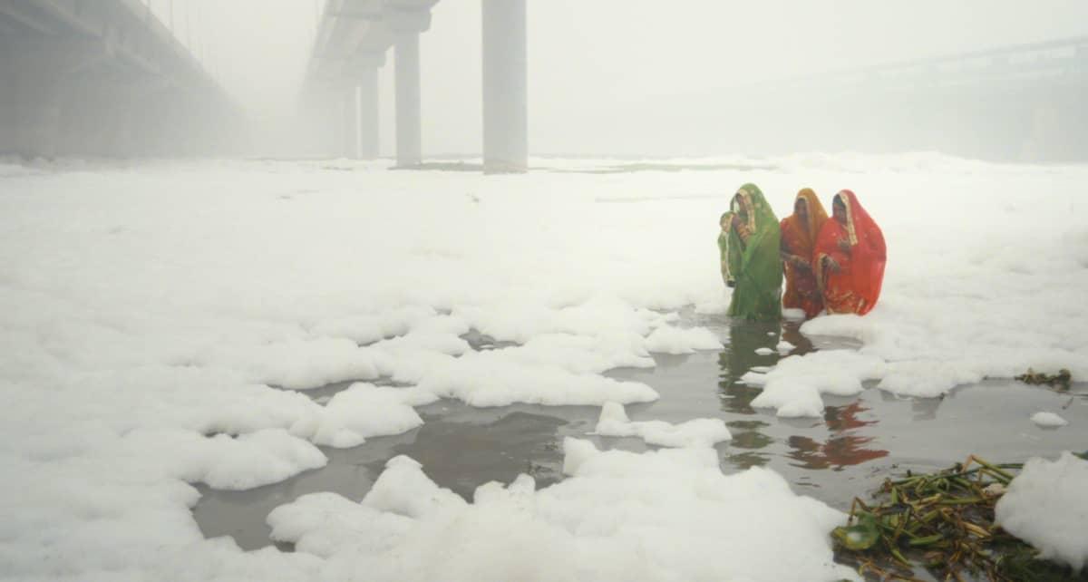 Intialaisia ihmisiä kahlaamassa lumisessa vedessä.