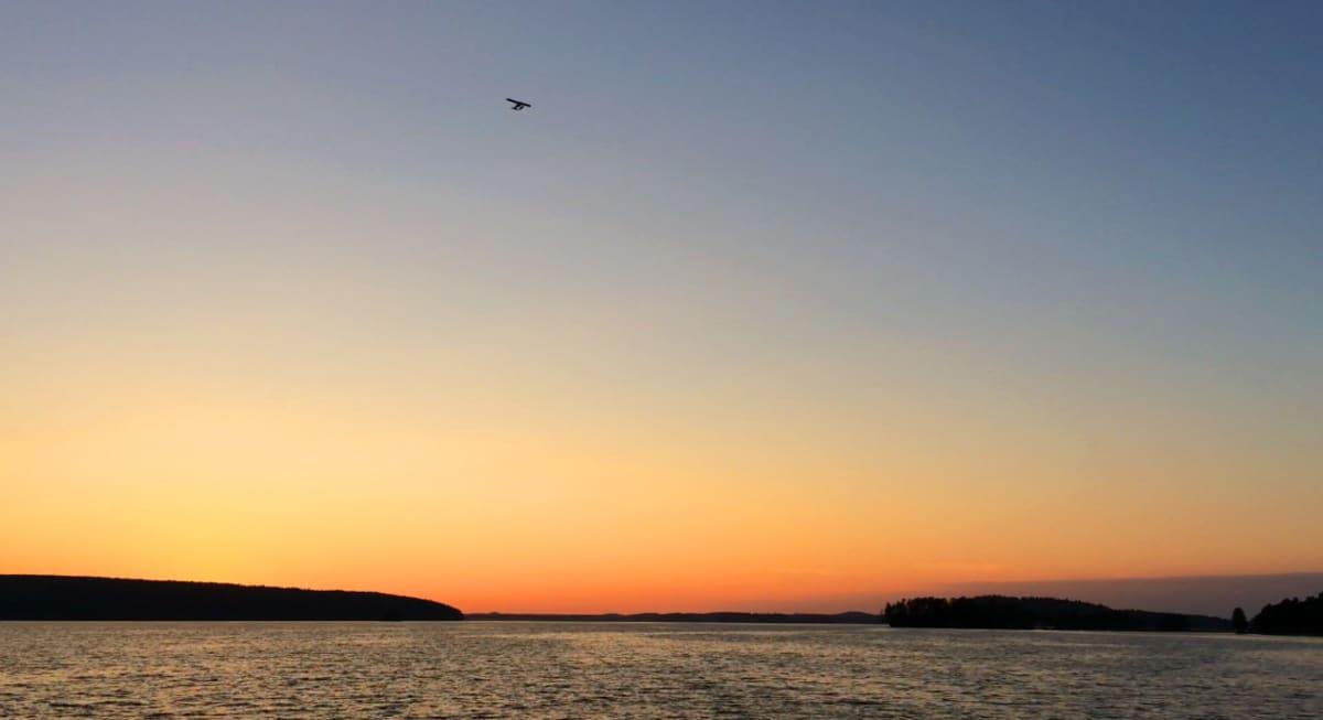 Pienkone lentää Vesijärven yllä Lahdessa, aurinko laskee horisonttiin.