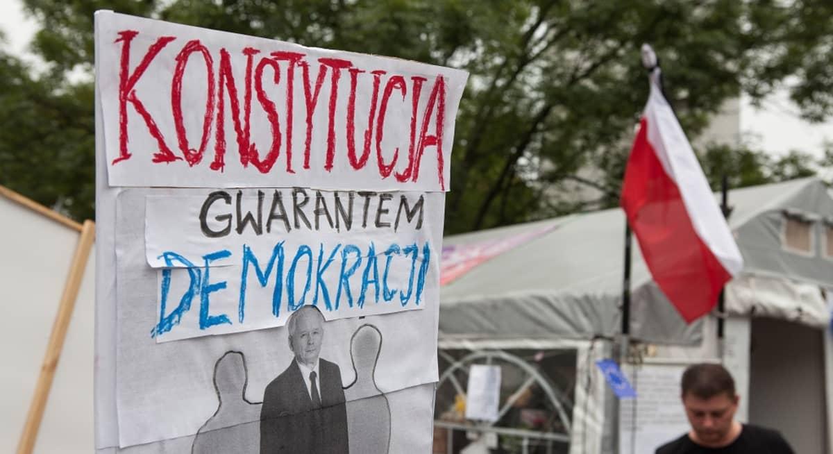 Mielenosoittajien kyltti, jossa teksti: konstytucja gwarantem demokracji.