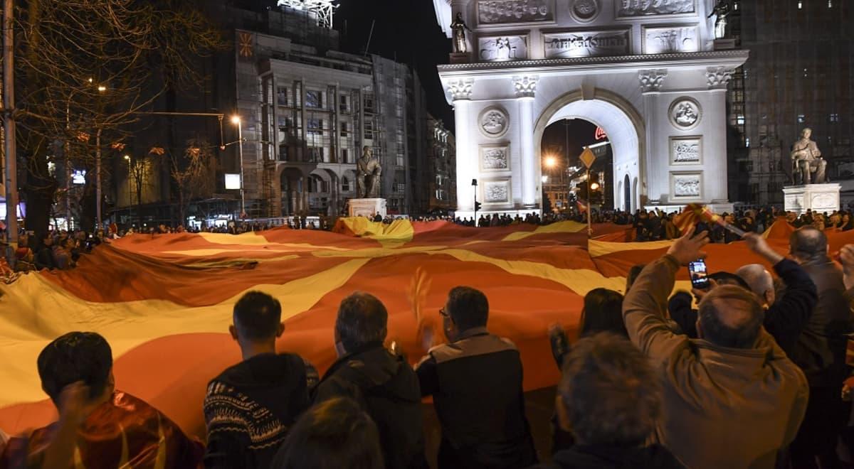 mielenosoittajia ja suuri makedonian lippu skopjessa