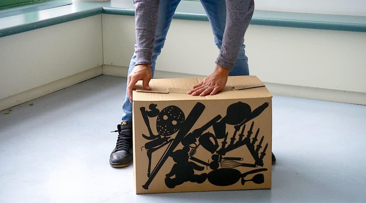 Mies pakkaa muuttolaatikkoa.
