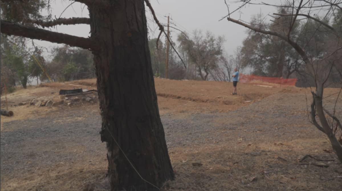 Paul Clement seisoo tyhjällä tontilla, jolla ennen oli hänen talonsa. Kuvan etualalla on mustunut puu.