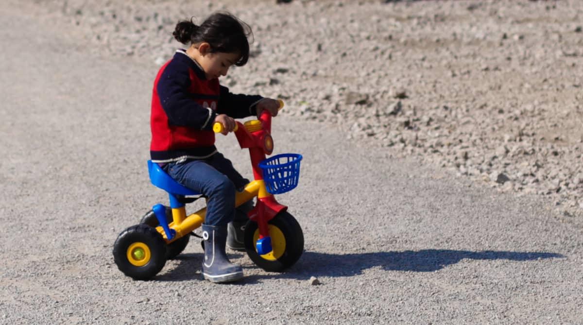 Lapsi leikkii kolmipyörällä