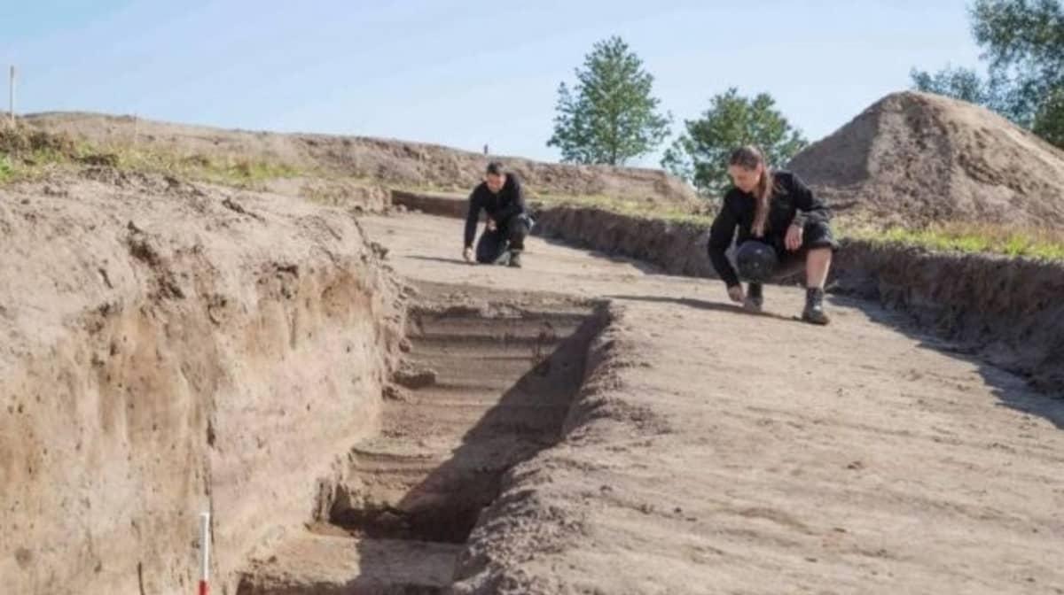 Kaksi tutkijaa puhdistaa kaarevassa kaivausojassa maata kaivauslastoilla.