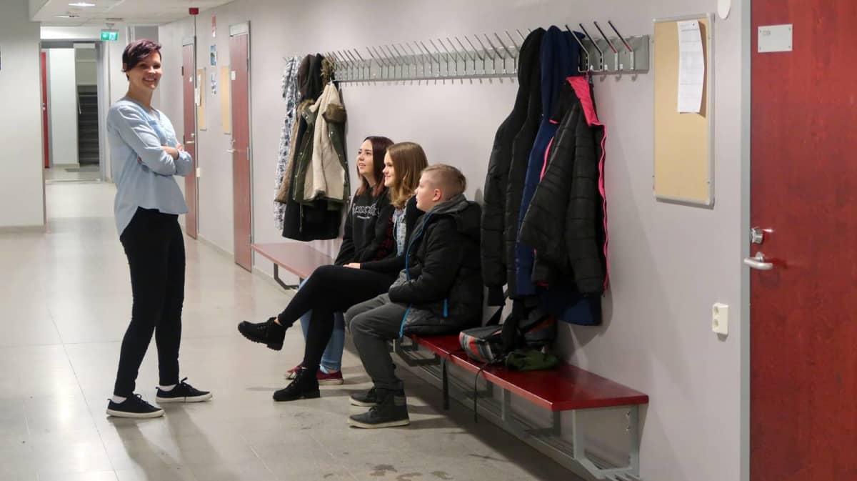 Outi Koskinen juttelee oppilaiden kanssa koulun käytävällä.