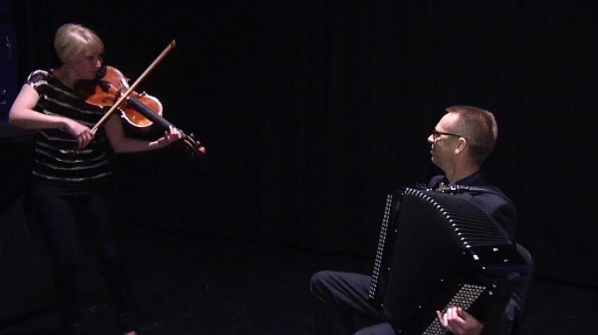 Mies soittaa harmonikkaa ja nainen viulua