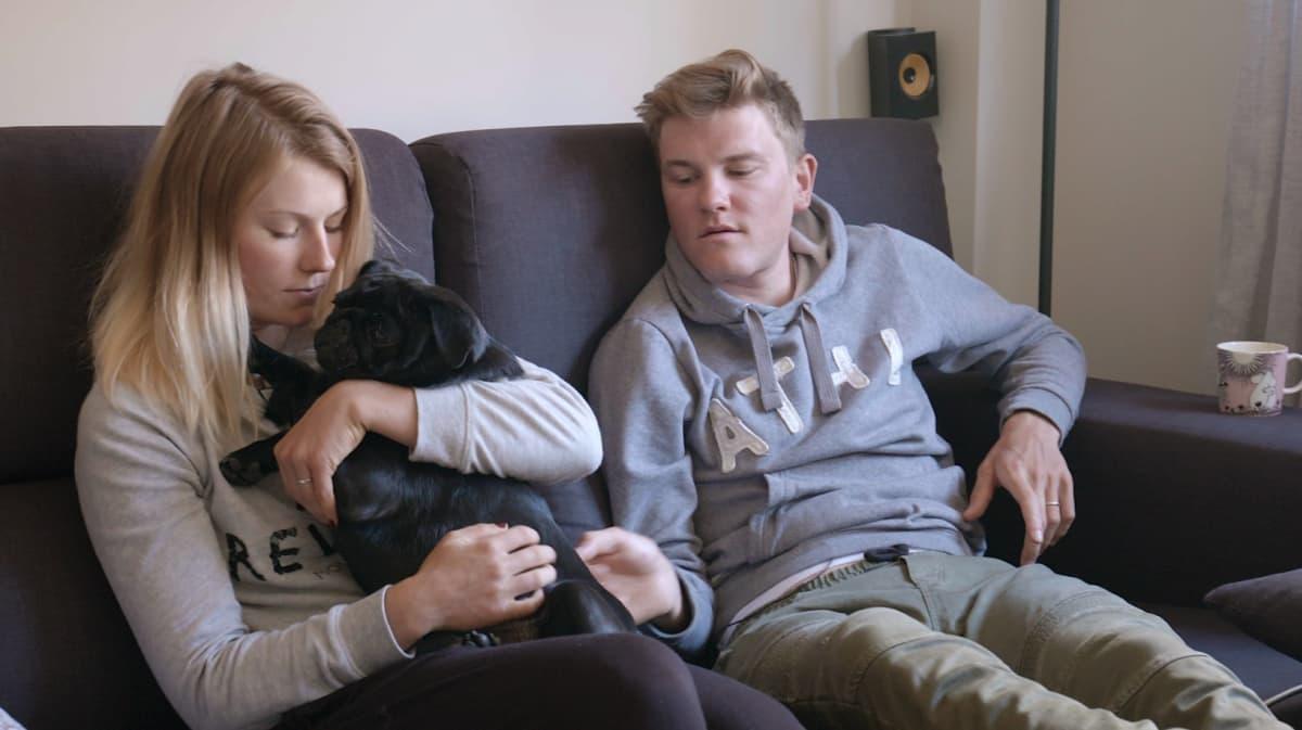 Lotta Lepistö ja Joonas Henttala sohvalla koiransa Karin kanssa.