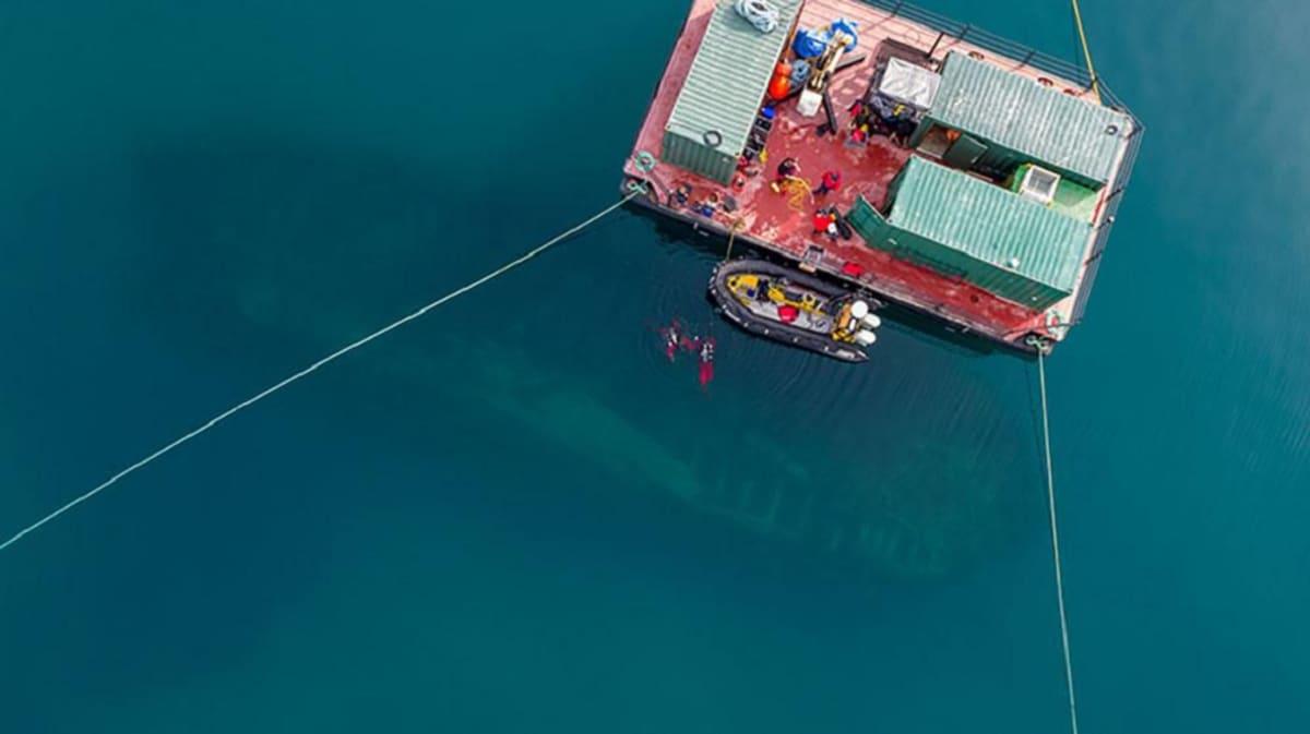 Ilmasta otetussa kuvassa tutkijoiden suuri lautta ja kumivene kelluvat pinnalla. Veden läpi häämöttää hylyn tumma hahmo.