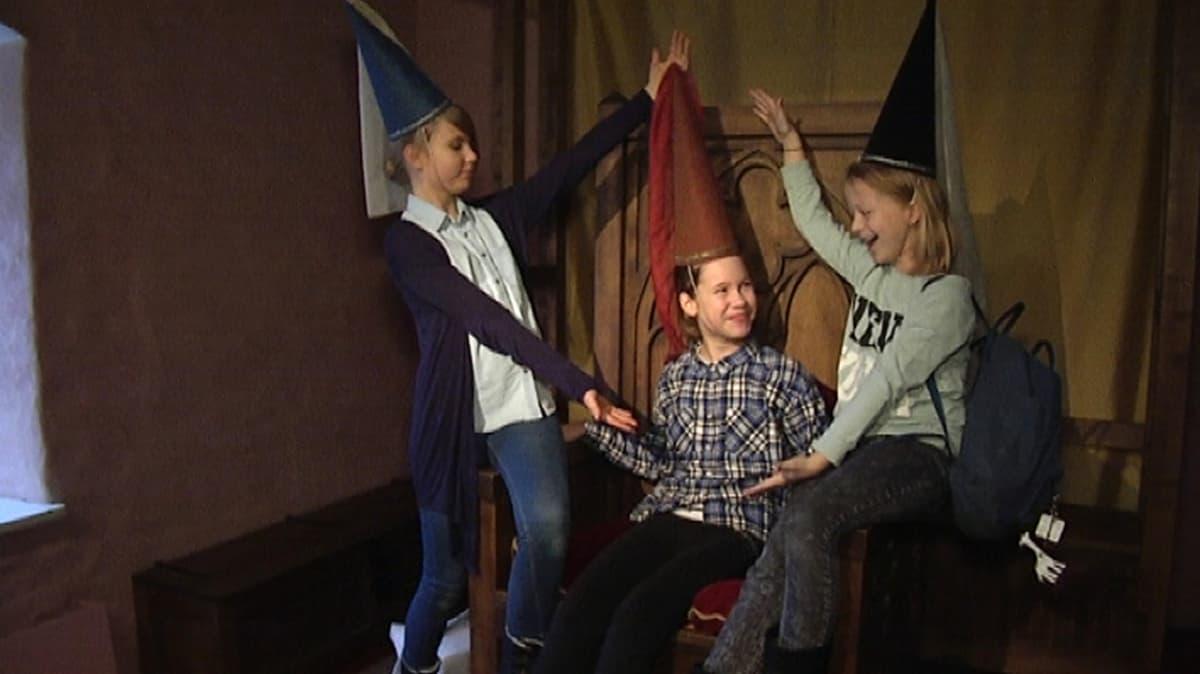 Koululaiset pukeutuneena linnanneidon hattuihin Turun linnassa.