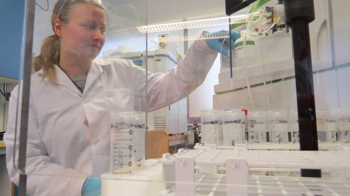 Tutkija tarkastelee mittauslaitetta laboratoriossa