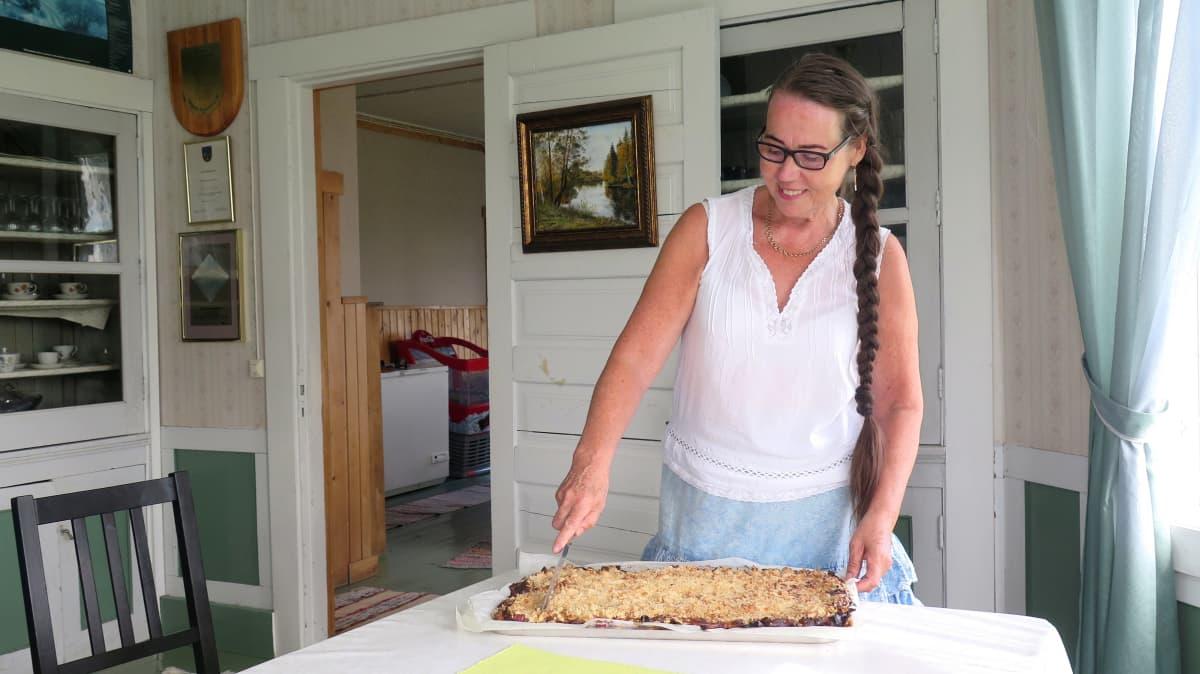 Katariina Pylsy leikkaa raparperipiirakkaa.