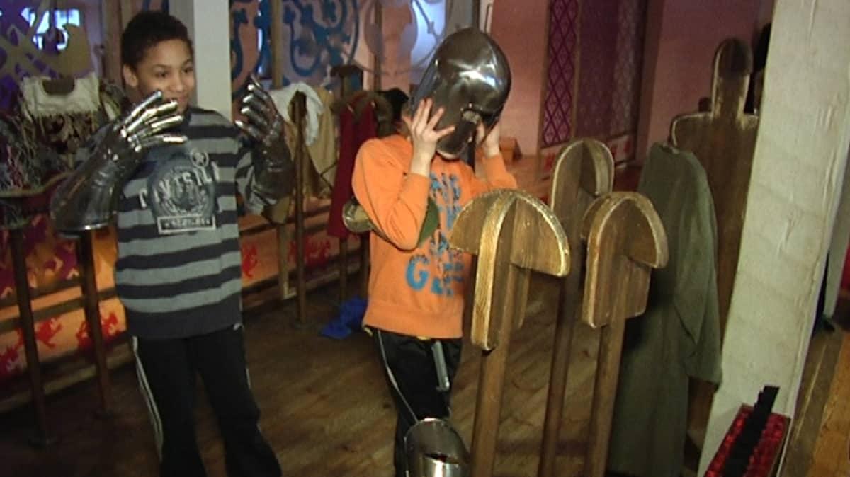 Koululaiset sovittavat ritarinvarusteita Turun linnassa.