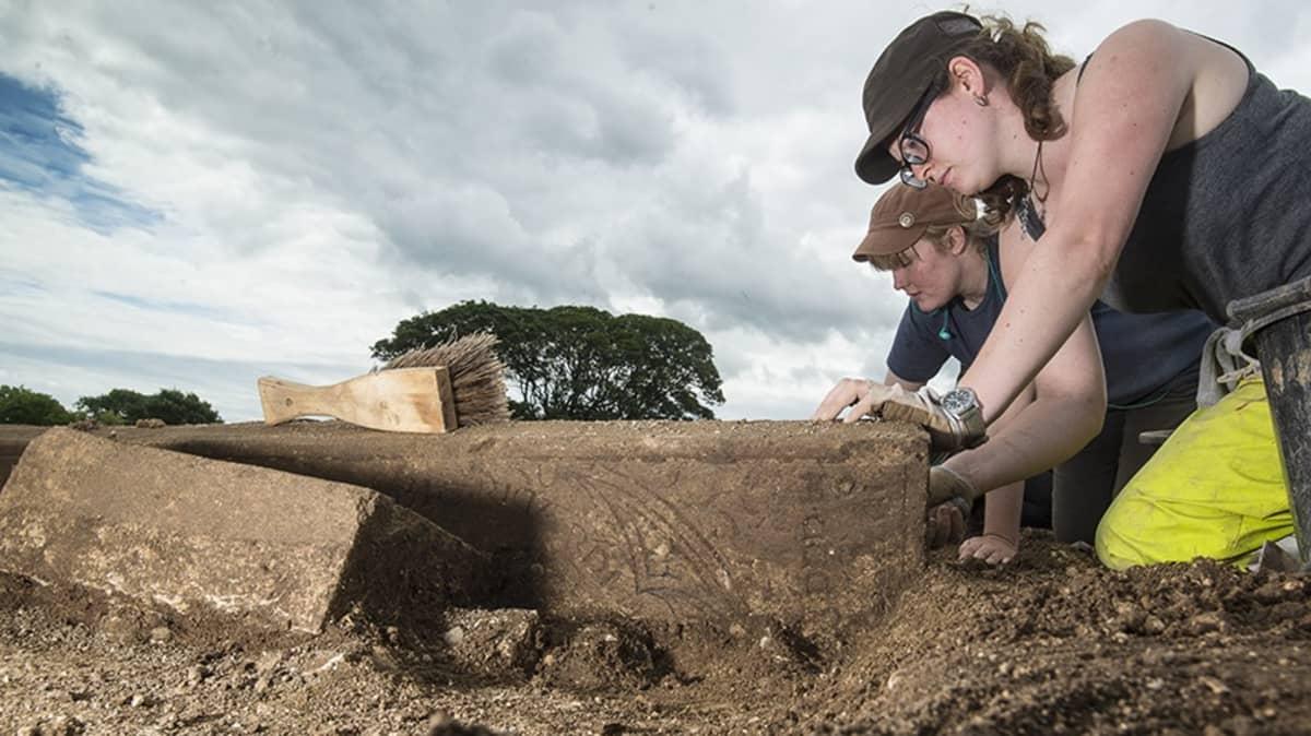 Kaksi nuorta arkeologia kaivaa maasta hautakiveä, jossa näkyy kaiverrusta.