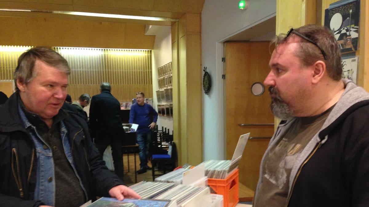 Levykauppias Pekka Nurminen hieroo kauppoja asiakkaan kanssa levymessuilla Kotkassa