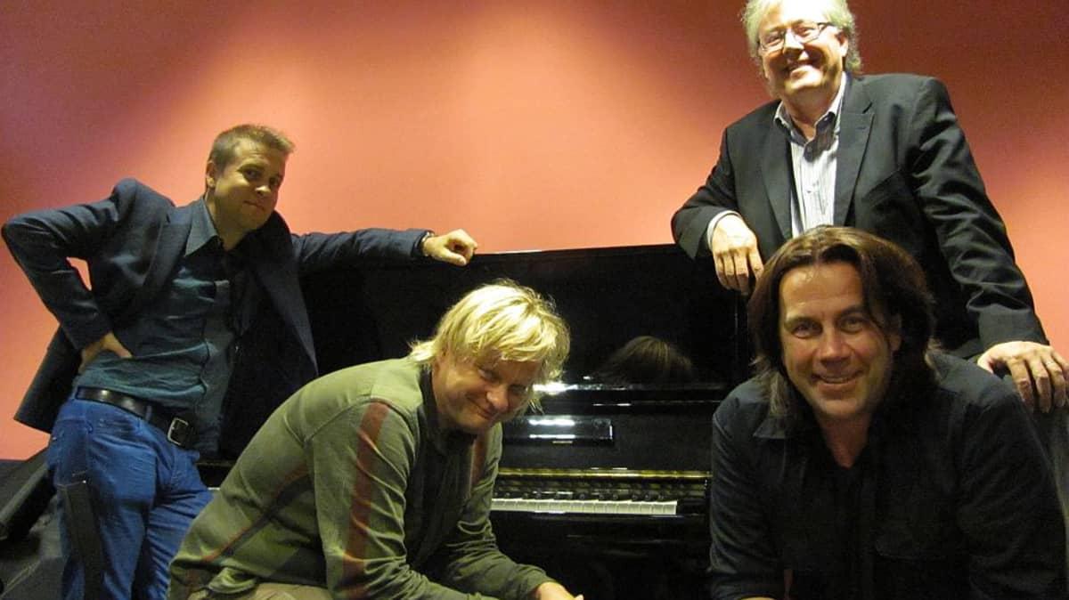 neljä miestä pianon ääressä