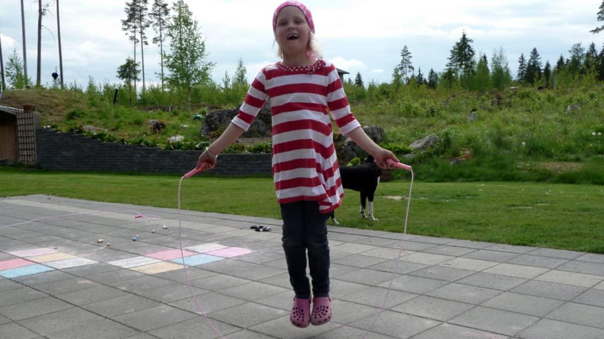 Tyttö hyppii hyppynarulla.