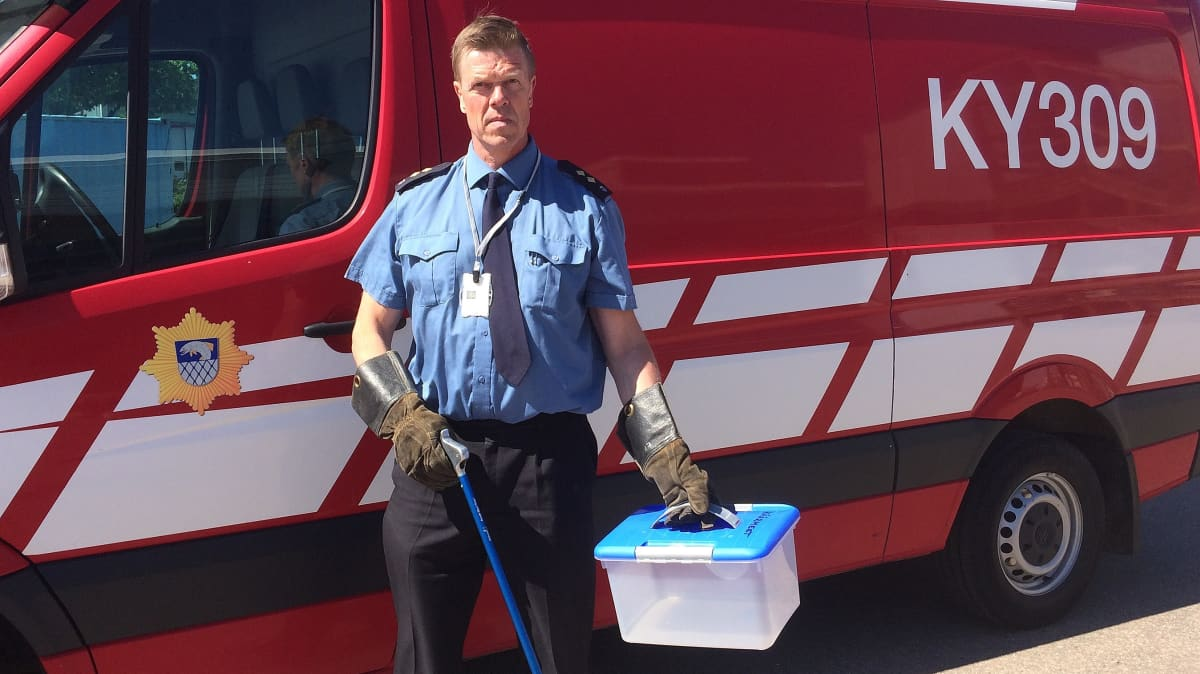 palomestari Juha Säämänen seisoo palolaitoksen pakettiauton edessä, kädessä paksut rukkaset ja käärmelaatikko, eläinpelastus