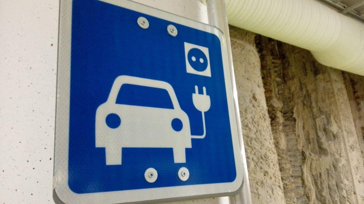 Sähköauton latauspisteen merkki parkkihallissa.