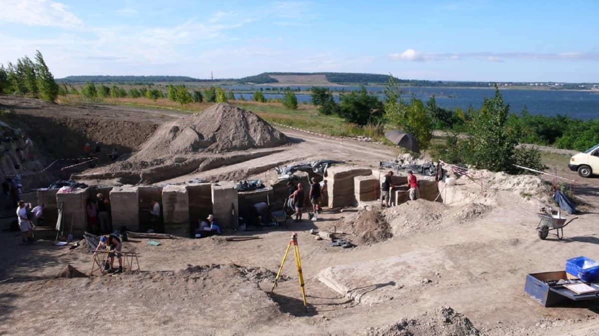 Arkeologinen kaivausalue, takana järvi.