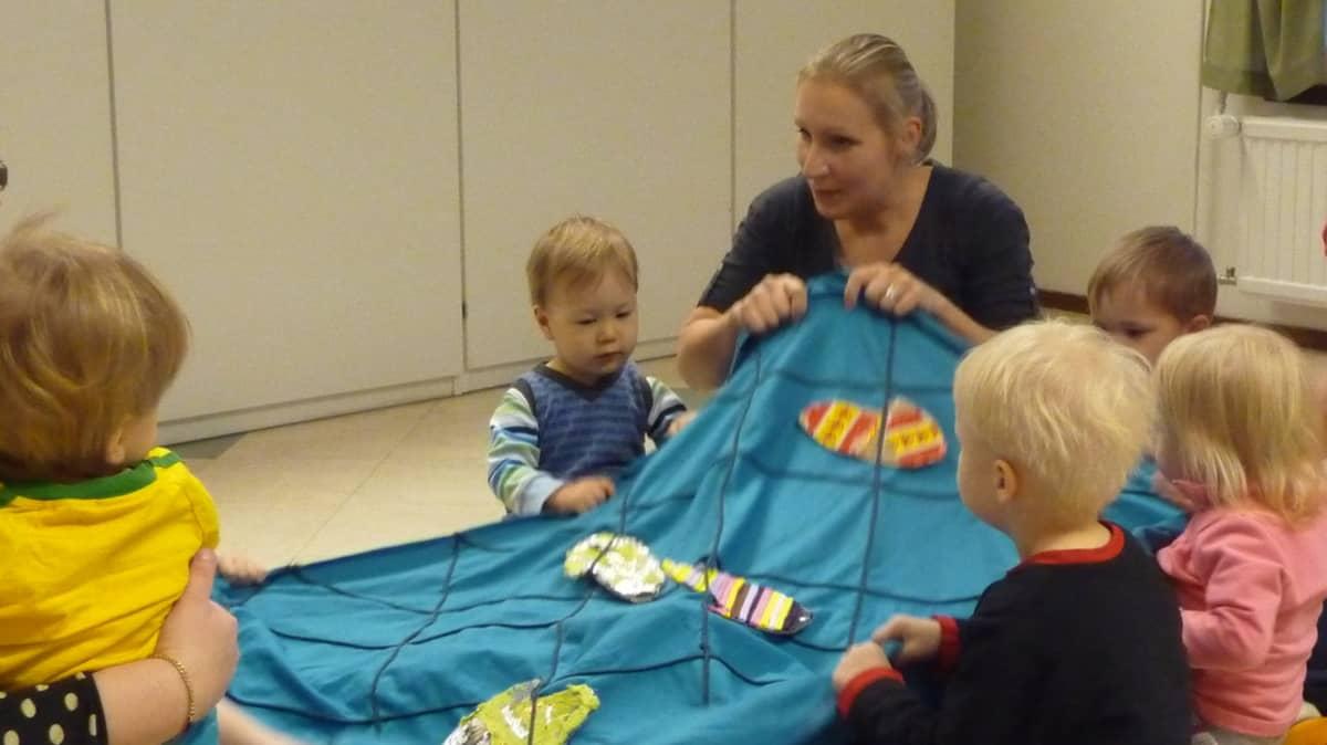 Sanataiteilija Anne Karjula loruttaa lapsia.