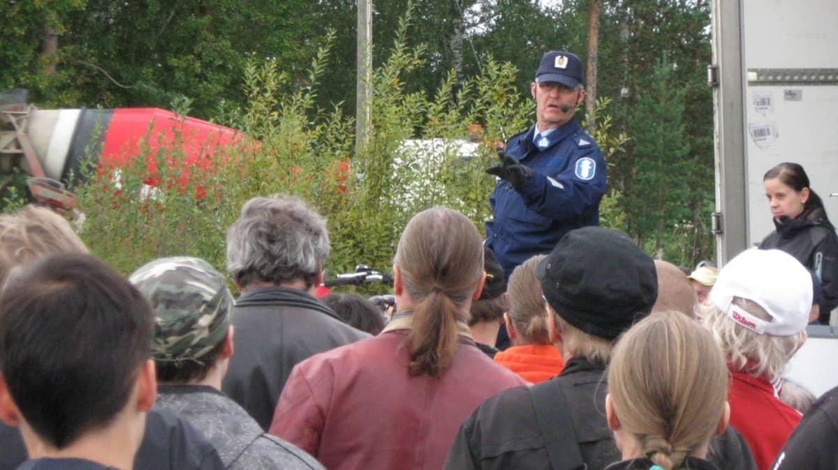 Poliisi pitää huutokauppaa rekan edustalla.