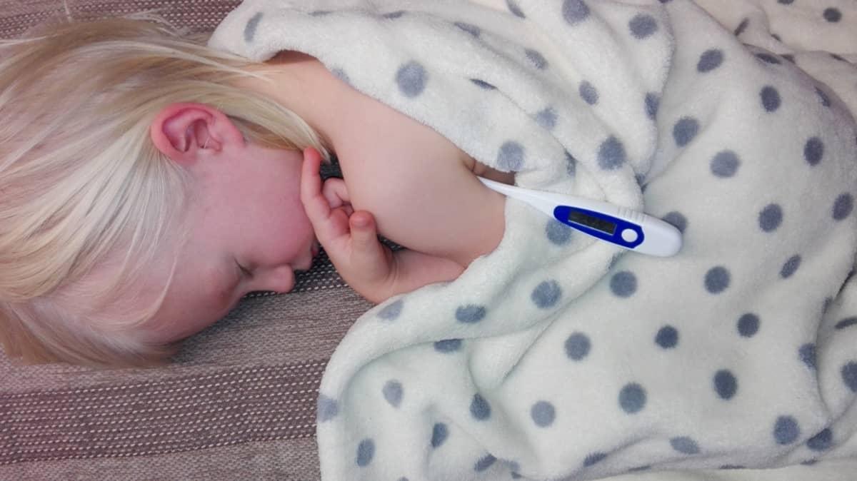 Punaposkinen lapsi nukkuu kuumemittari kainalossa.
