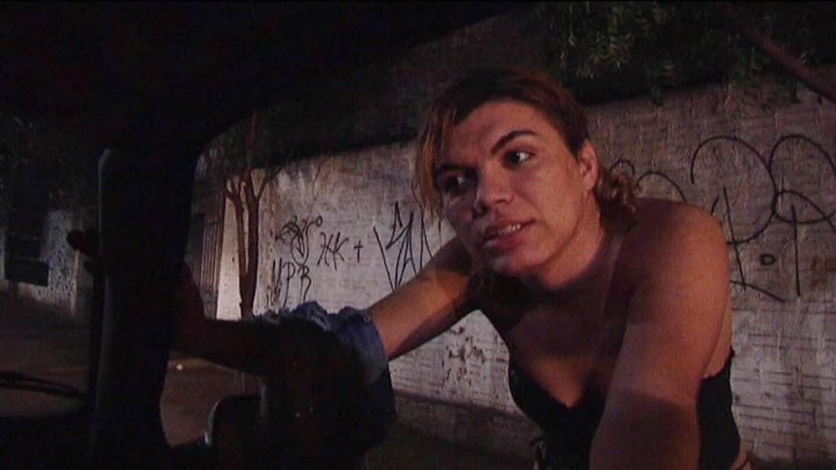 Brasilialainen prostituoitu kumartuu auton ikkunaan.