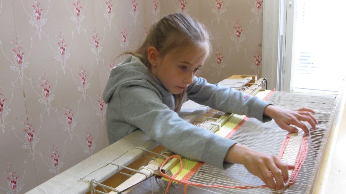 8-vuotias Iira Heikkinen kutomassa mattoa.