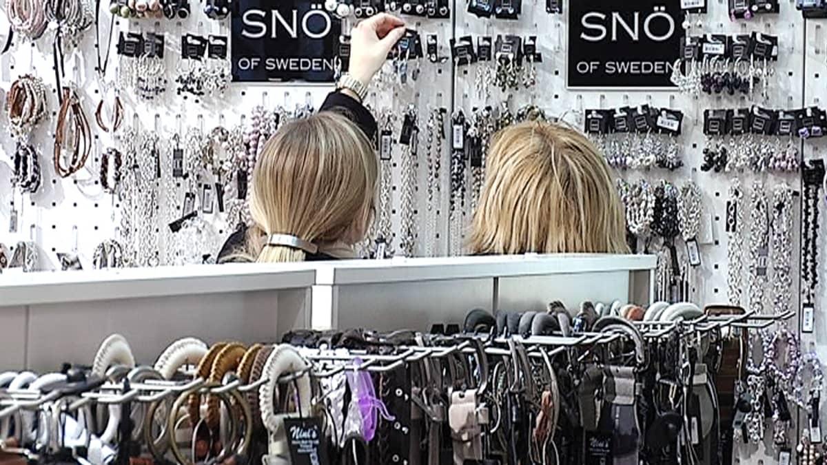 Kaksi naista tutkailee korvakoruja tavaratalon koruosastolla.