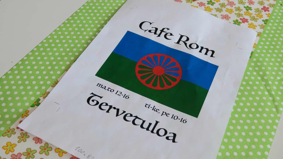A4-mainoslappu pöydällä. Cafe Rom romanikahvilan mainoksessa romanien lippu.