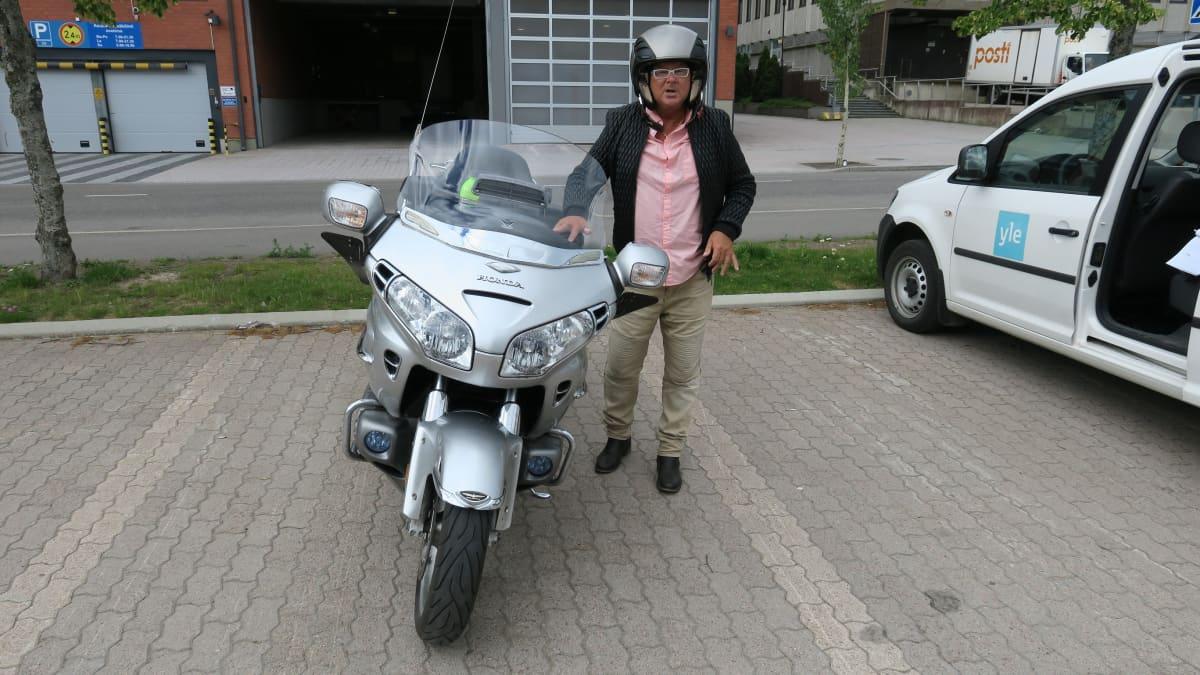 Mies moottoripyöränsä vieressä.