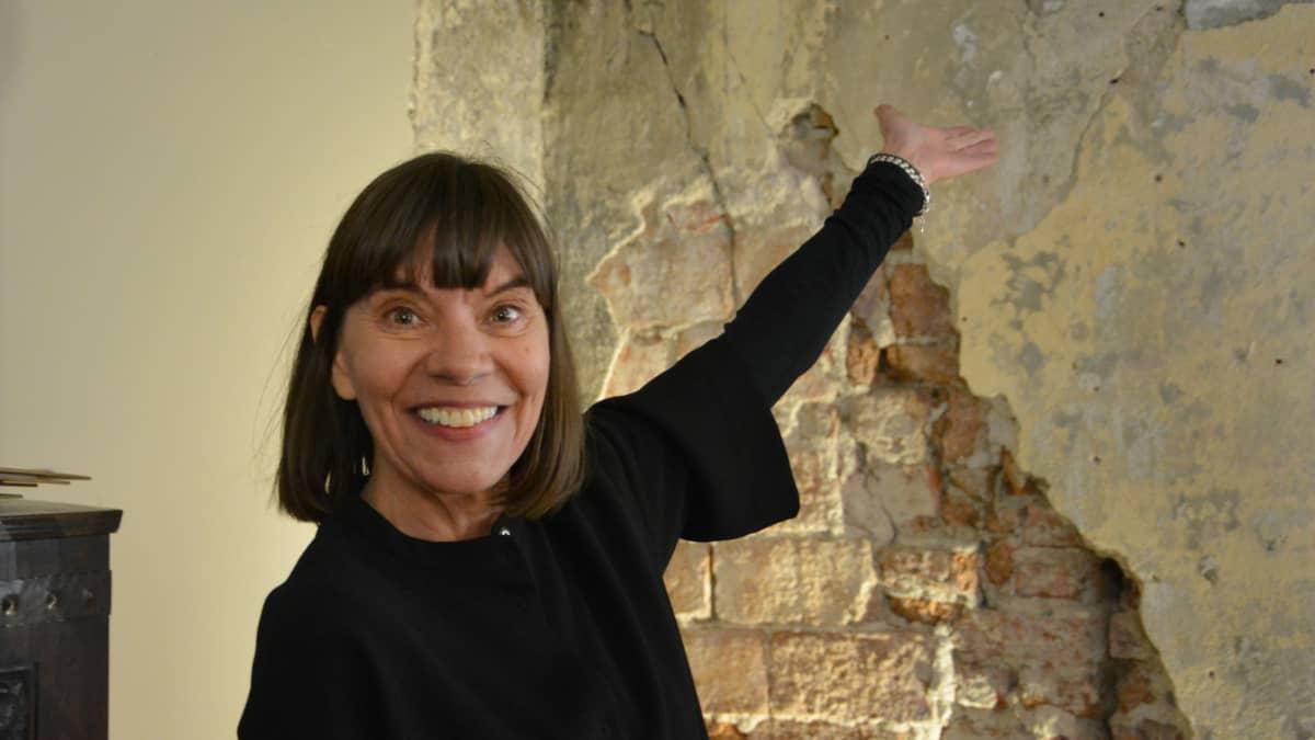 nainen osoittaa seinää