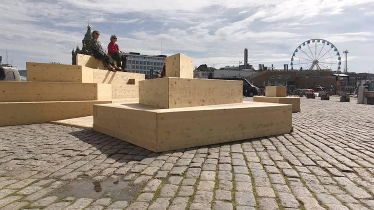 Helsingin kauppatorilla avattiin kaksi uutta oleskelutilaa ihmisten vapaaseen käyttöön. Puinen saariryhmä sijaitsee Suomenlinnan lauttaterminaalin läheisyydessä.