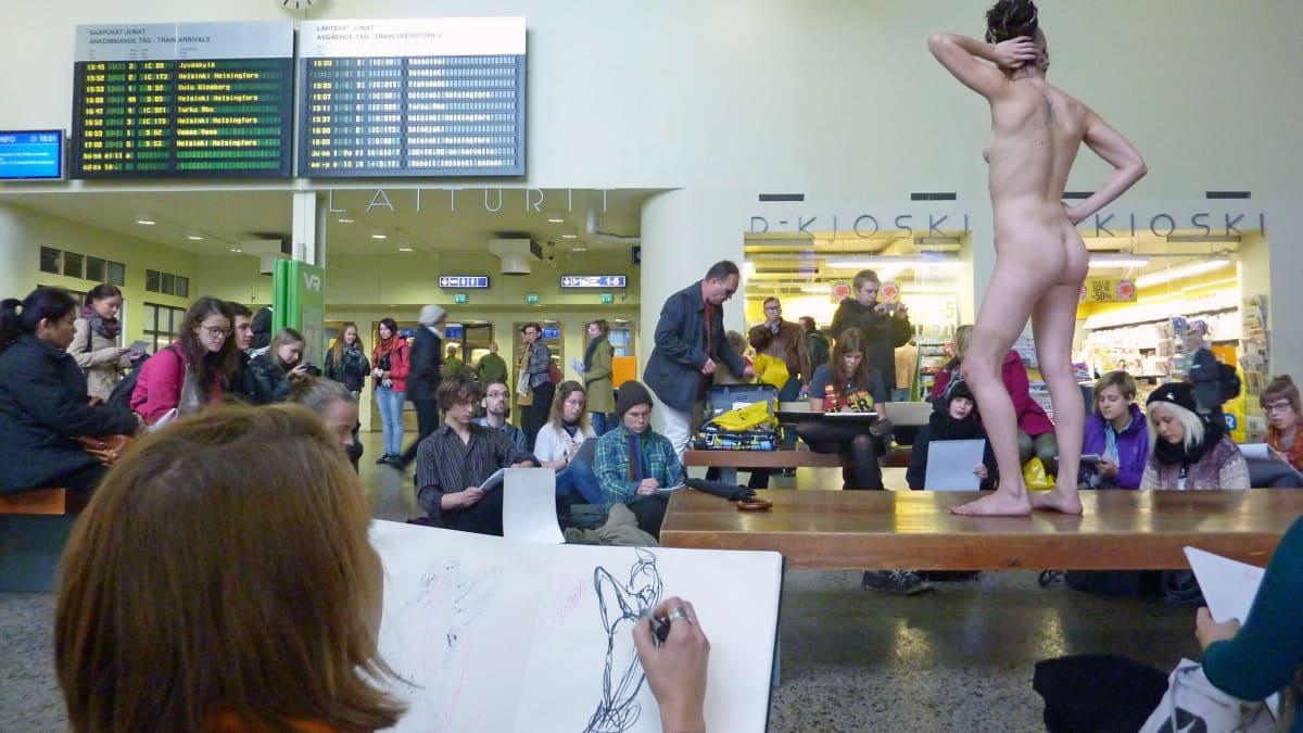 Opiskelijat piirtävät penkillä seisovaa alastonmallia.