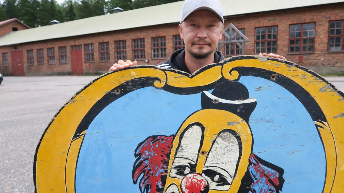 Carl Jernström junior esittelee roskalavalta pelastettua pellekylttiä tulevan Sirkusmuseon pihalla.