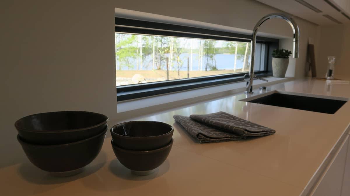 Tämän keittiön sisustusta määritteli ikkunoista avautuva järvimaisema. Vaaleat seinät ja kaapit antavat tilaa vuodenaikojen mukaan vaihtelevalle luonnon värimaailmalle.