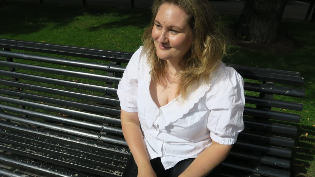 Vivi Mikkonen istuu penkillä puistossa.