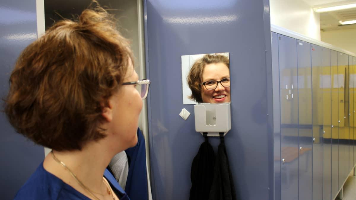 Sairaanhoitaja Riitta Mertanen sairaalan pukuhuoneessa