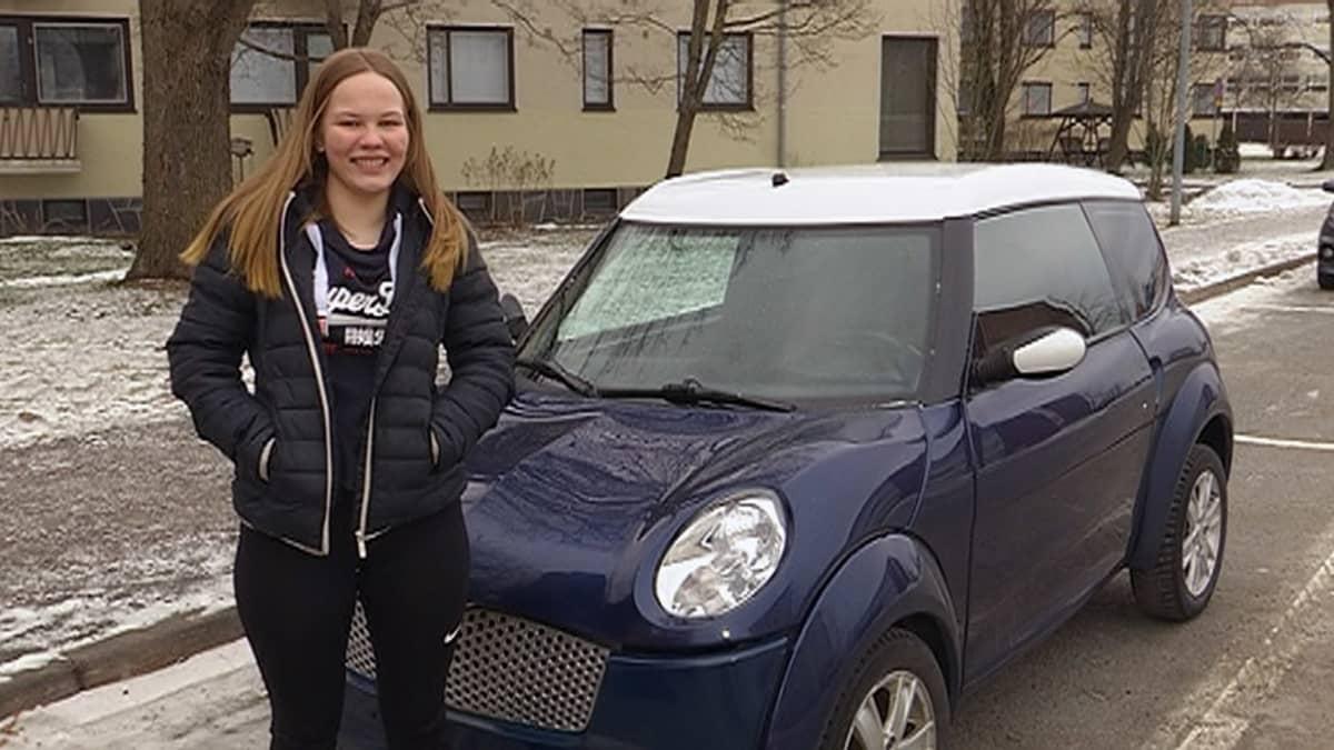 Anni Mäntyvaara seisoo mopoauton vierellä