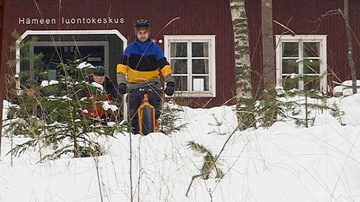 Mies pyöräilee fatbikella talvisessa maastossa takanaan Hämeen luontokeskus