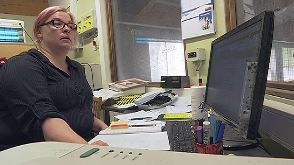 Johanna Heinonen tietokoneen ääressä navetalla