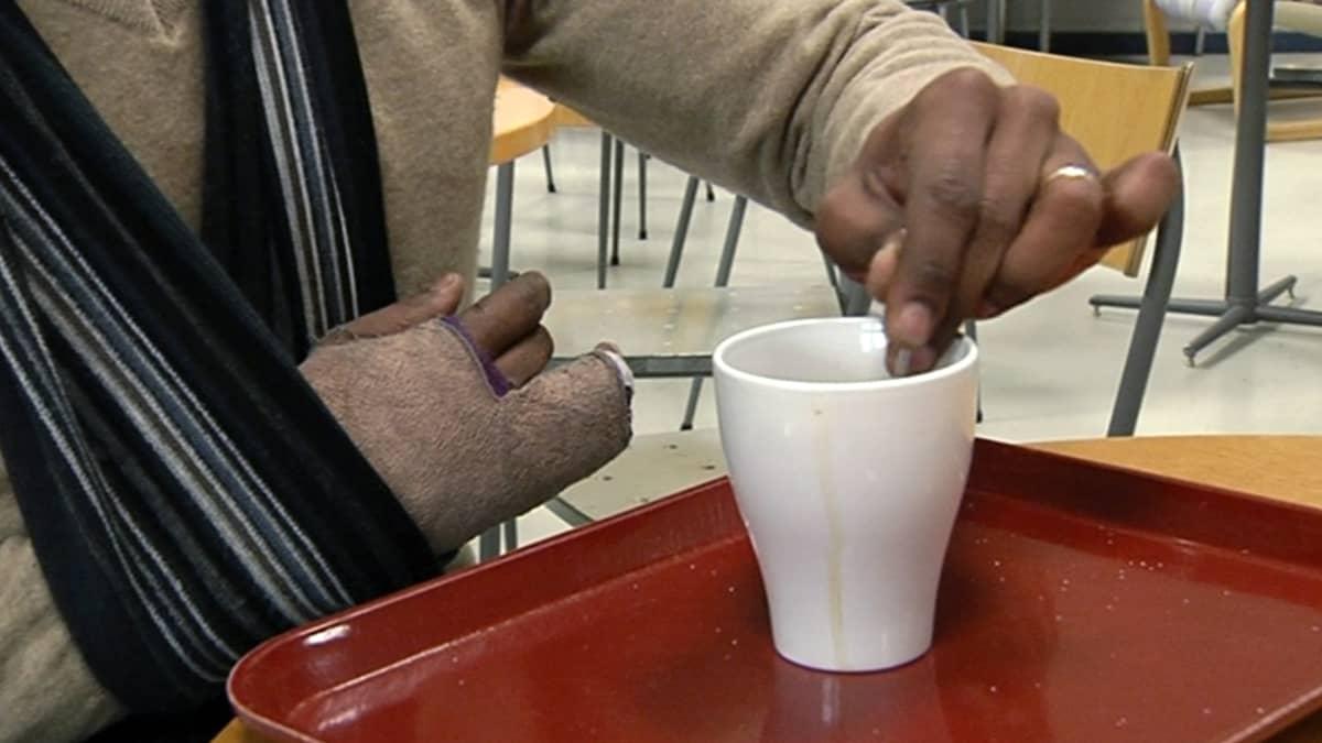 Mies sekoittaa kahvia.