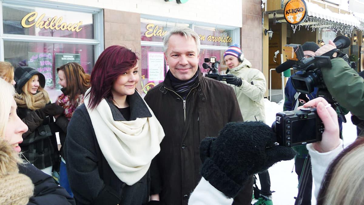 Presidenttiehdokas Pekka Haavisto poseeraa kuvaajille punatukkaisen nuoren naisen kanssa.