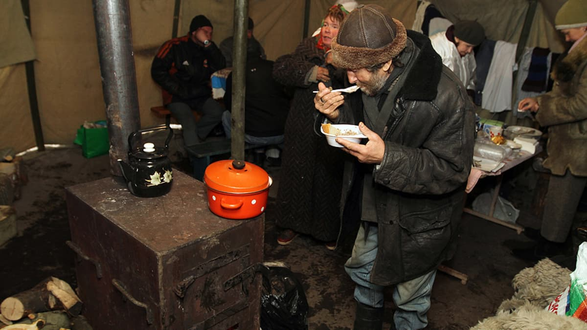 Koditon ukrainalaismies syö hyväntekeväisyysjärjestön tarjoamaa päivällistä näiden Donetskiin kodittomien suojaksi pystyttämässä teltassa.