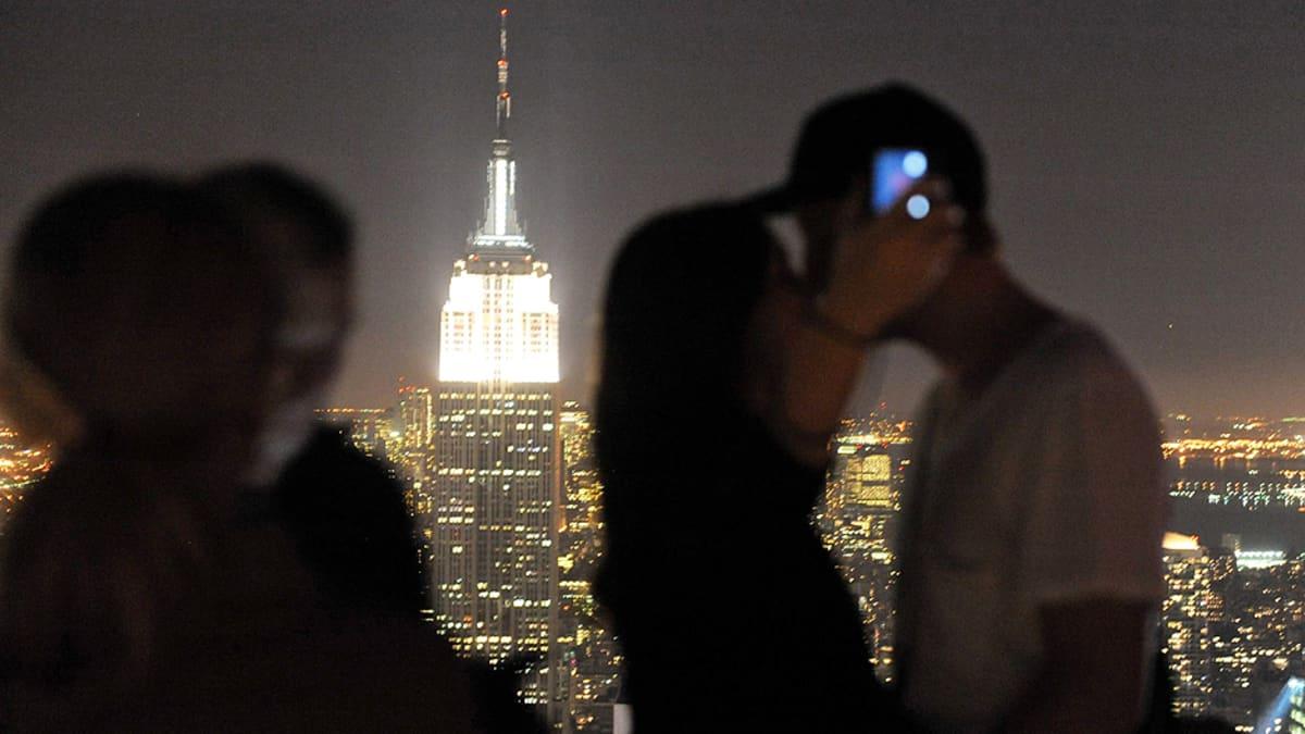 Pariskunta suutelee Rockefeller Center -rakennuksen näköalatasanteella valaistu Empire State Building taustallaan.