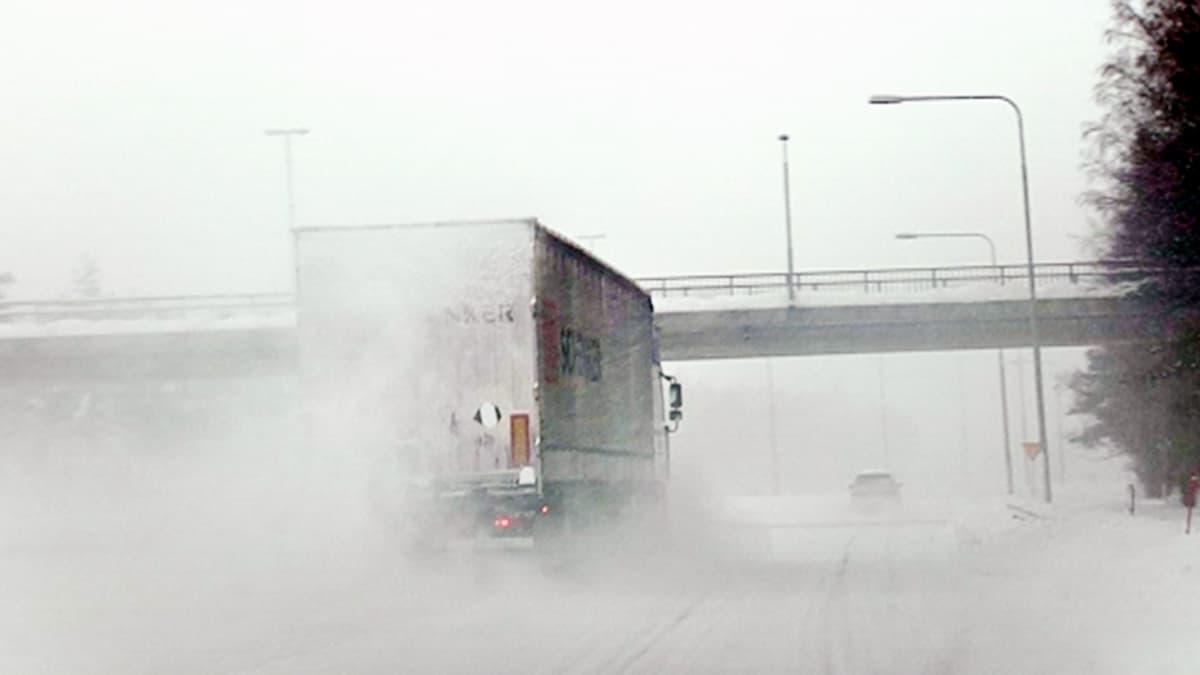 Autoja liikenteessä moottoritiellä lumisateessa.