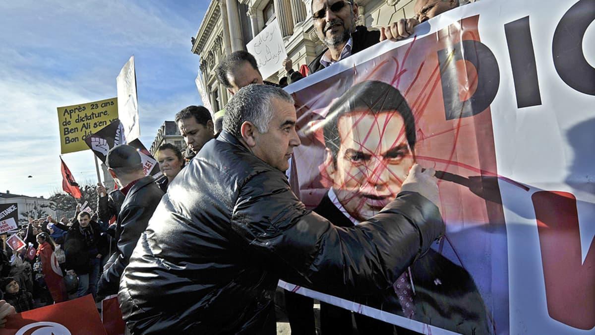 Mielenosoittaja sotkee Tunisian entisen presidentin kuvaa banderollissa.