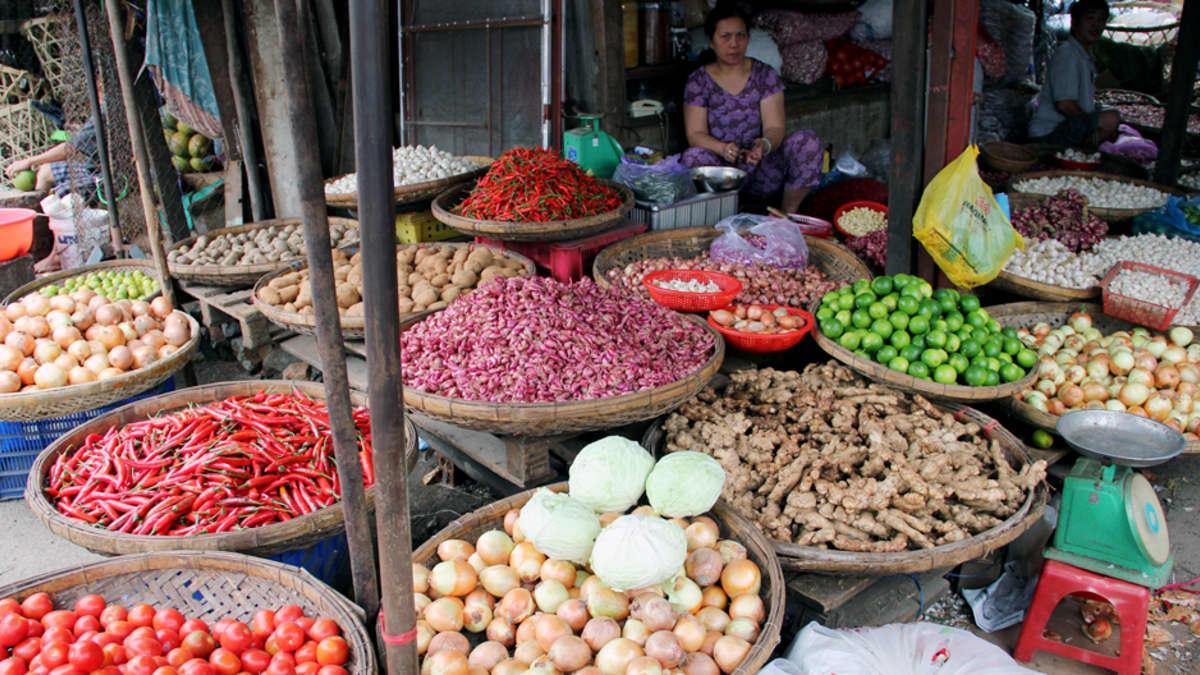 Vietnamilainen nainen myy vihanneksia Nha Trangin torilla.